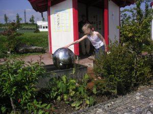 geomantische Positionierung des Brunnens und Ausrichtung des Infohauses