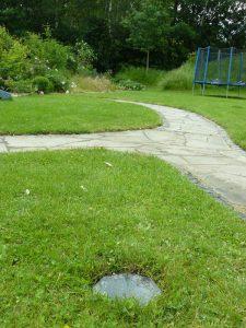 Eine geomantische Lithopunktion im energetischen Zentrum des hinteren Gartenbereichs