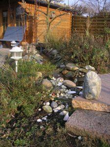 Gestaltungsdetails im Geomantiegarten: Bachlauf, Beleuchtung, Kunstwerk und Bepflanzung